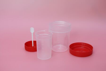 Jars for analysis on a pink background. Containers for feces and urine. The containers are empty. Concept of passing tests in a medical laboratory.