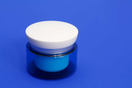 Blue jar of cosmetic cream on a blue background. Body lotion in a jar. Moisturizing gel for the skin. Anti-aging cream.