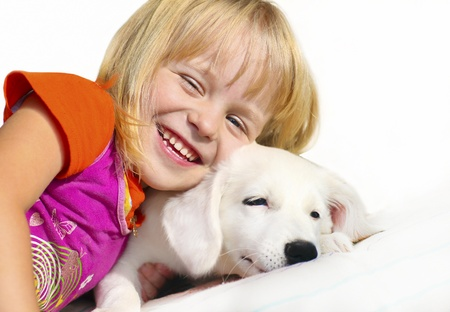 Little girl with blond hair plays with a puppy  Stock Photo