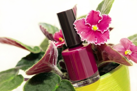 caring for: Nail Polish with Violet flower on a white background.