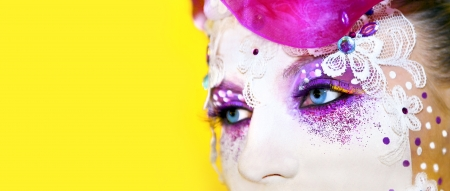 Makeup in the form of masks with eyelashes, rhinestone, accessories, silver glitter on a yellow background
