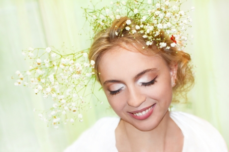 A beautiful young girl with make-up and a flower in her hair. photo
