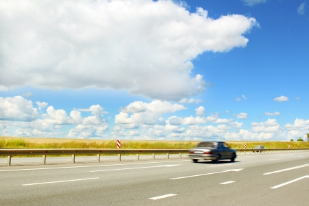 moves: The car moves along an asphalt road in cloudy weather in the summer
