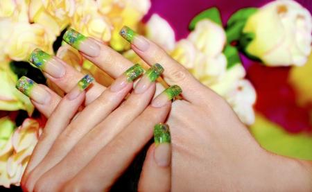 long nail: Unghie in acrilico con l'aiuto di pezzi di acrilico verde e sabbia dorata Archivio Fotografico