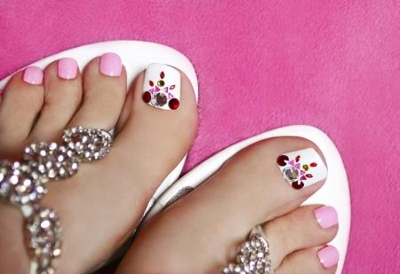 pedicura: Pedicura en las piernas de las mujeres s en un color rosa y blanco con diamantes de imitación Foto de archivo