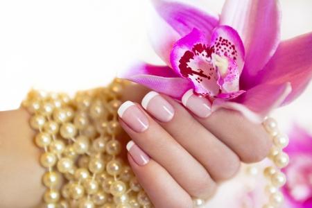 Manicura francesa a la mano de una mujer con una orquídea y cuentas Foto de archivo