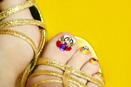 Art coverage with crystals on the nail women s feet in sandals on a yellow background  Stock Photo