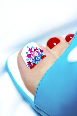 pedicure: Art pedicure with crystals on women s legs with rhinestone sandals blue on a white background  Stock Photo