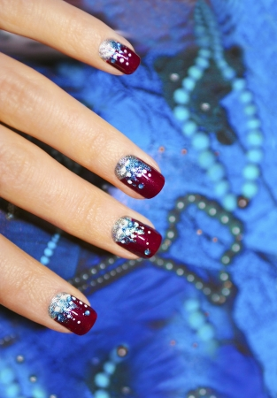 Festive nail design for short nails on a blue background.