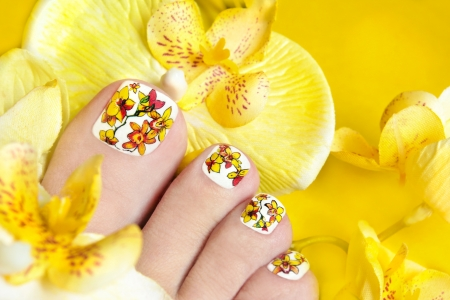 Pedicure with yellow orchids in the women s legs on a yellow background