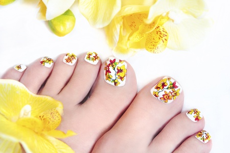 Flower pedicure with yellow orchids in the women s legs on a white background  Zdjęcie Seryjne