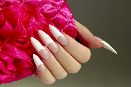 Long French nails with white manicure on a woman s hand with pink accessory on a dark background