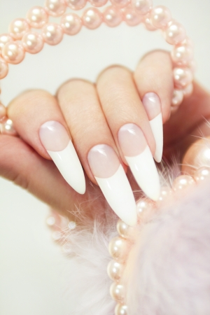 Long French manicure with pearls and the fur on a gray background.