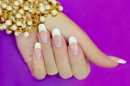 French manicure with a beautiful decoration on the wrist of the lilac background.
