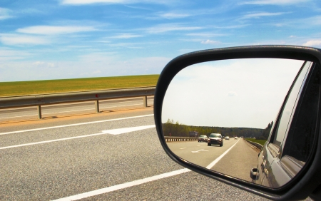 Reflection of the movement of vehicles in the mirror of cars on the road in the spring weather is Sunny.