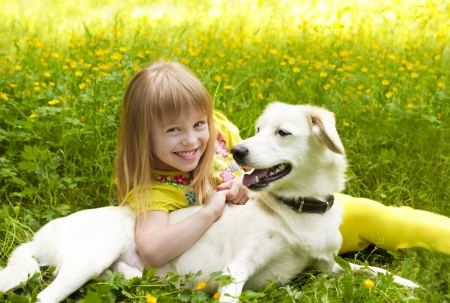 Little beautiful girl hugging her dog in the summer of nature  Stock Photo