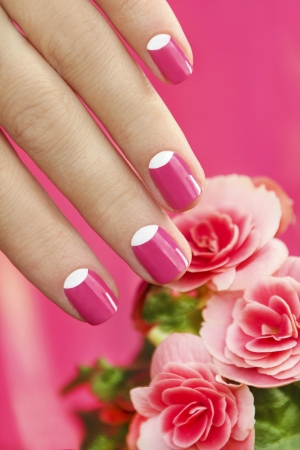 women s health:   Beautiful manicures on short nails woman with a flower on a pink background