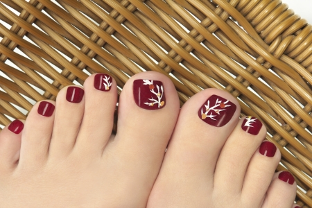 Burgundy pedicure with a picture of the women s nails on a background