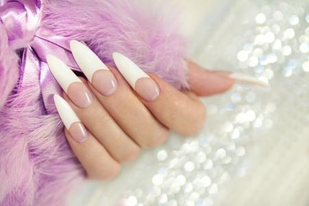 uñas largas: Manicure francés siempre se puede apilar con el acrílico en la mano de una mujer s sobre un fondo brillante con piel
