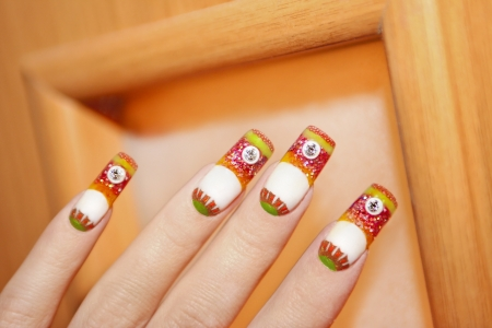 Nail design is completely made using colored acrylics on orange wooden background