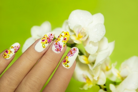 Art nail design with picture of orchids on a woman s hand on a green background  Stock Photo
