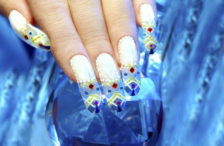 Aquarium design nail in the festive winter decorated with rhinestones on the blue blurred background