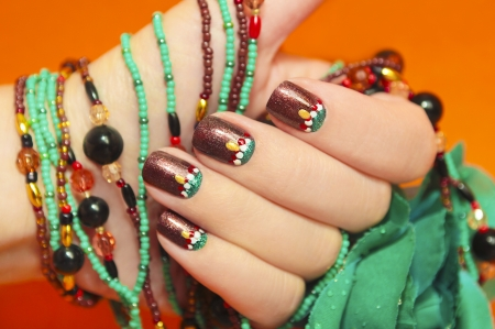 nail design:   Women s nails are covered with brown varnish with the design of white,red and turquoise points on an orange background with a bracelet made of beads in the tone of the nail