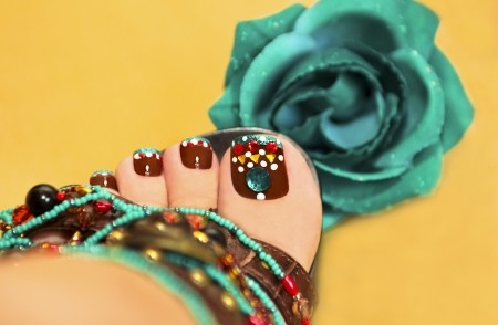 women s feet: Beautiful art nail design women s feet in sandals with a rose on a yellow background  Stock Photo