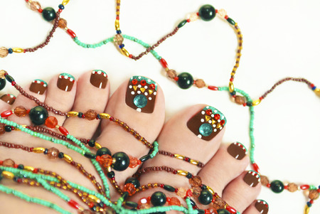manicure and pedicure: Nice pedicure with rhinestones on female legs embellishment from beads on a light background