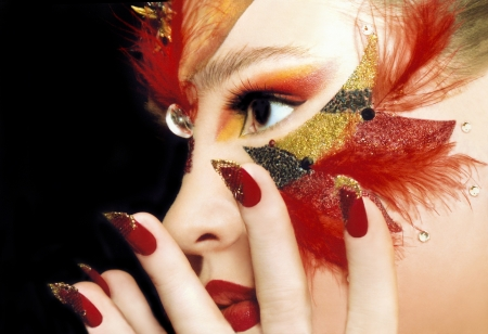 Beautiful sight of the girl in the red make-up,red lips and nails,sequins and feathers