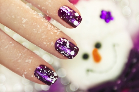 christmas manicure:   Christmas new year winter manicure with the design of the white snowflakes on violet brilliant varnish for the nails on the background of the snowman  Stock Photo