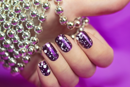 sparkles: Snow manicure with the design of the white crumbs on violet brilliant varnish for the nails
