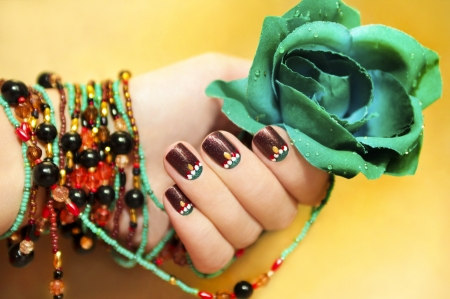 Ethnic motifs on the nails female young hands with beaded bracelet with turquoise rose on a yellow background