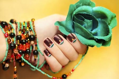 uñas pintadas: Motivos étnicos en las uñas de manos de una mujer joven con brazalete de perlas con turquesa rosa sobre un fondo amarillo