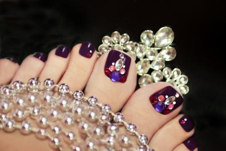 Holiday elegante pedicura púrpura con joyas de fantasía sobre un fondo negro con joyas Foto de archivo