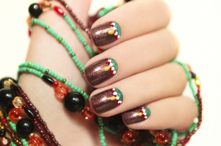 Ethnic art design of the nails on a woman s hand embellishment from beads on a white background