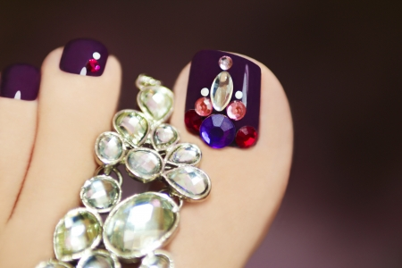 Elegant pedicure with rhinestones on purple nail varnish female foot on a dark background