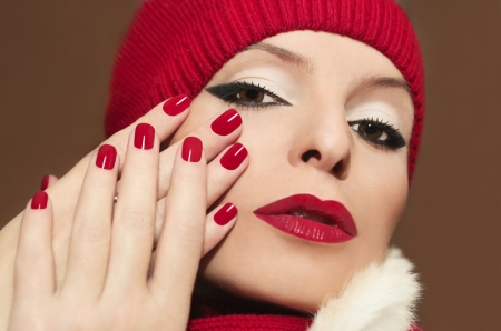 A beautiful young girl with red lipstick and nail Polish on a brown background in the hat  photo