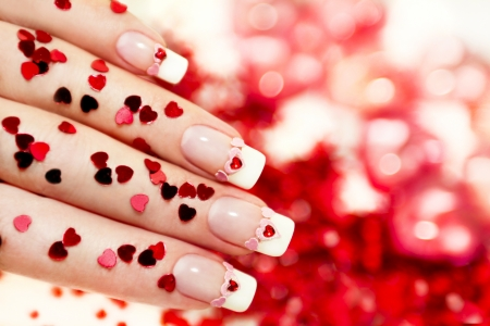 Beautiful holiday manicure with a red heart and with sparkles in the shape of a heart in my hand, and background