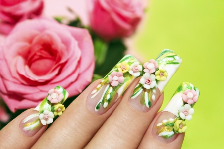 Art nail design with acrylic roses on the French manicure on a green background with roses