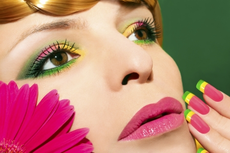 Beautiful colorful makeup and nails with gerberas on a young girl on a green background close up