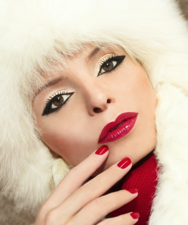 Winter makeup with red lips and fingernails on a beautiful young girl  photo