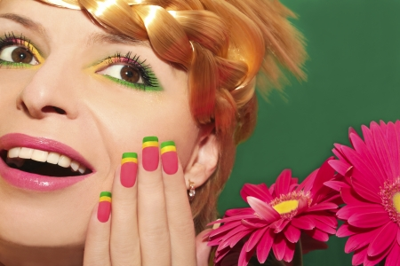 Beautiful summer makeup with pink lips and colorful nails on a beautiful young girl with braids on his head and near the pink gerberas on a green background  Stock Photo