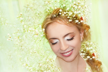 Beautiful girl in the spring image with flower gypsophila in your hair on a light green background  photo