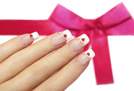 skin art: Beautiful French manicure with pink and red hearts on the nails