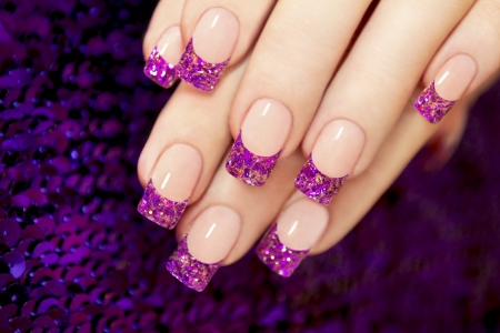 nail design: Aquarium nail with blue chips and gold sequins in female hands