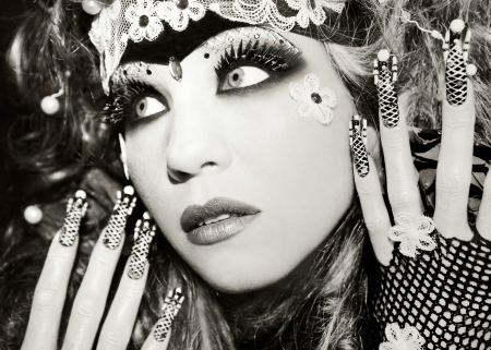 Portrait of a young beautiful girl in the make-up with black eyes and with artificial long nails with beads on the end of the nail   photo