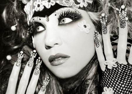 black eyes: Ritratto di una giovane e bella ragazza nel make-up con gli occhi neri e con lunghe unghie artificiali con perline sulla fine del chiodo