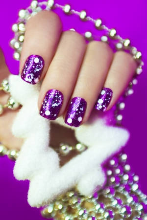 saturated color: Beautiful snow manicure with purple varnish and white crumb with the accessory in the form of a tree