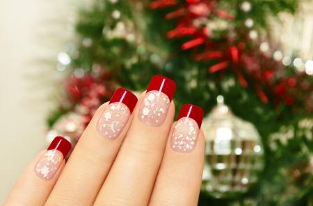 Manicura invierno con laca roja y fichas blancas sobre el fondo del árbol de Navidad Foto de archivo